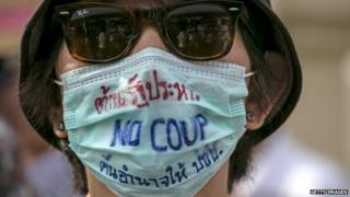 A Thai woman wearing a mask which reads 'no coup'