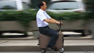 He Liang rides his motorised suitcase