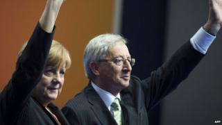 German Chancellor Angela Merkel (L) and former Prime Minister of Luxembourg, Jean-Claude Juncker (R) waving at a rally in Berlin on 5 April 2014