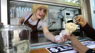 Caitlyn Faircloth, a worker with Molly Moon's Homemade Ice Cream, hands out free ice cream next to a tip jar, 2 June 2014