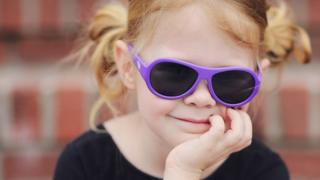 A young girl wearing Babiator sunglasses