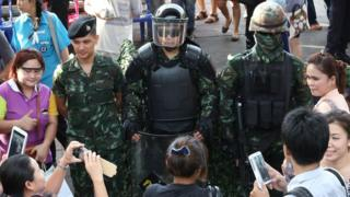 """People take photos of Thai special forces officers during an event called """"Return Happiness to Thai People"""" at Bangkok's Victory Monument in Thailand on Wednesday, 4 June, 2014"""