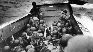 A landing barge, tightly packed with helmeted soldiers, approaches the shore at Normandy, France, on D-Day.