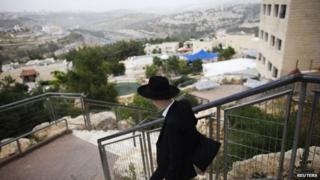 An ultra-Orthodox Jewish man walks through the settlement of Ramat Shlomo (5 June 2014)
