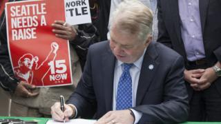 Seattle Mayor Ed Murray signs the city's minimum-wage increase on 3 June, 2014