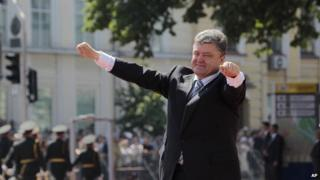 Ukrainian President Petro Poroshenko lifts his arms in greeting after the inauguration ceremony in Sophia Square in Kiev