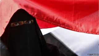A woman sitting under a flag in Tahrir Square, Egypt