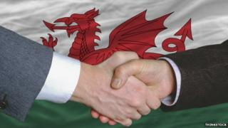 Shaking hands and Welsh flag