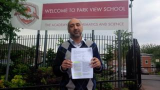 Arshad Malik, parent at Park View School, pictured outside its gates with the Ofsted report which put the academy in special measures