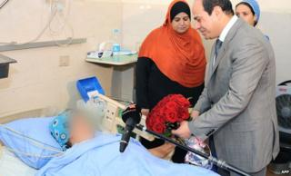 A handout picture released by the Egyptian presidency shows President Abdel Fattah al-Sisi visiting a hospital where the victim of a sexual assault is receiving treatment