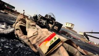 The jacket of an Iraqi army uniform lies on the ground in front of a burnt out Iraqi army vehicle east of the northern city of Mosul, on 11 June 2014,