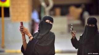 Saudi women take pictures on smartphones