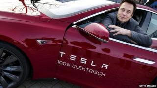Tesla head Elon Musk poses in one of his electric cars.