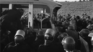 Police surround the last coach to be stopped from racing round the field near Stonehenge where violence erupted in 1985