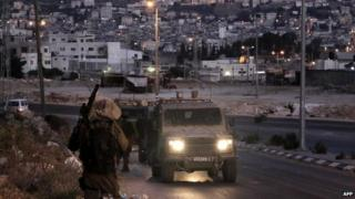 Israeli soldiers take part in an arrest operation in the West Bank town of Nablus early on 18 June 2014