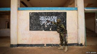 Kenyan troop points to a mural