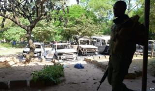 Kenya police observe the remains of burnt-out cars at a police station in Mpeketoni on 16 June 2014