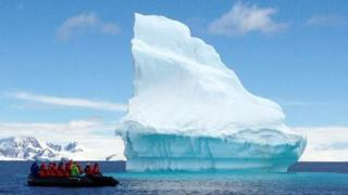 Tourists view an iceberg in Kinnes Cove