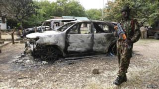 A policeman stands guard near destroyed cars in the coastal Kenyan town of Mpeketoni - 18 June 2014