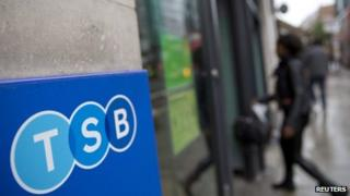 A woman walks into a branch of TSB bank in London