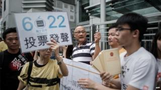 Demonstrators supporting the Occupy Central movement display placards asking residents to cast ballots for the 22 June during a protest outside Beijing's representative office in Hong Kong, on 11 June.
