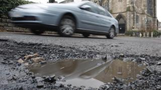 A car driving past a pothole