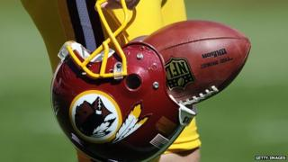 A player carries a Redskins helmet with a football in it.
