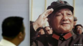 A man looks at a portrait of former Chinese leader Deng Xiaoping