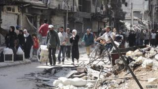 File photo: Residents walk as they receive aid at the Palestinian refugee camp in Yarmouk, south of Damascus 20 May 2014