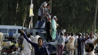 Supporters of Pakistani Muslim cleric Tahirul Qadri, leader of Pakistan Awami Tehreek (PAT) stand on a police armored car after clashing with security forces at Benazir International airport as they gathered to receive their leader in Islamabad, Pakistan, Monday, June 23, 2014.