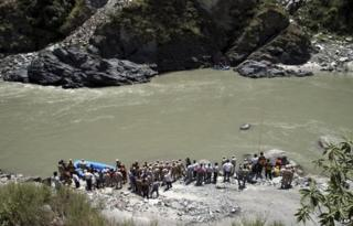 Indian rescue personnel gather on the banks of the Beas River during a search operation in Kullu