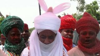 The new emir of the northern Nigerian city of Kano Lamido Sanusi (C) walks in Kano on 9 June 2014