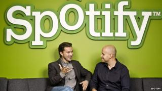 Spotify founders sitting in front of logo