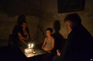 People sit in a bomb shelter in the besieged rebel stronghold of Sloviansk, eastern Ukraine, 22 June