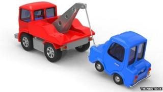 Toy car being towed by toy truck