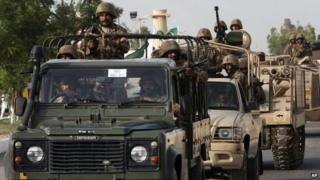 Pakistani army troops ride military vehicles following an operation launched against the Taliban in North Waziristan, in Karachi, Pakistan, Monday, June 16, 2014.