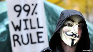 """An Occupy Wall Street protestor holds up a sign that reads, """"99% will rule""""."""