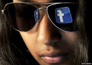 A woman with the Facebook logo reflected on her sunglasses