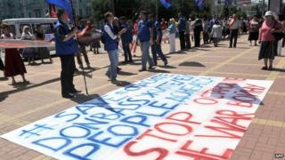 """People stand in front of a sign reading """"Save Donbass people - Stop the war"""" at a rally in the eastern Ukrainian city of Lugansk on 29 June 2014"""