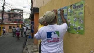 "Employees of the Dominican Ministry of Public Health stick posters on a wall during an information campaign to prevent the spread of the mosquito which transmits the Chikungunya virus, in the district of ""La Agustinita"", in Santo Domingo, on May 30, 2014"