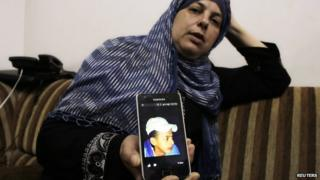 Suha, mother of Mohammed Abu Khdair, shows a picture of her son on her mobile phone at their home in Shuafat, an Arab suburb of Jerusalem on 2 2014.