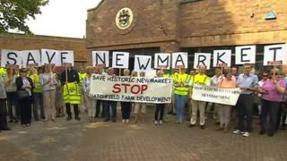 Protestors gather before a meeting to decide whether homes should be built in Newmarket