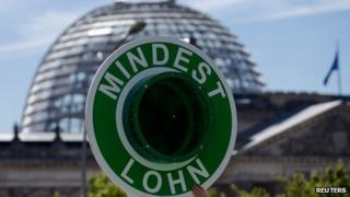 A campaigner holds a sign in front of the Reichstag, demanding a minimum wage