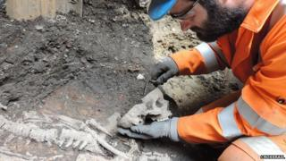 A Crossrail worker excavates a skeleton
