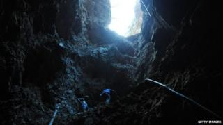 Gold miners look for gold inside an informal mine in the mountains of San Juan Arriba, 130 km south of Tegucigalpa, on 7 February, 2012