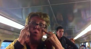 A screengrab from a YouTube video show shows a woman making a slitty eye gesture