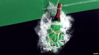 A bottle of champagne smashing against a ship