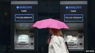 A woman shelters under an umbrella as she walks past cash machines outside a Barclays branch.