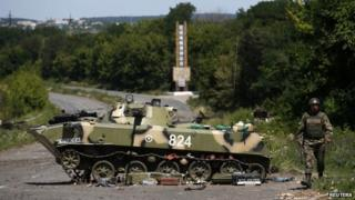 Ukrainian soldier walks near a destroyed armoured vehicle at Sloviansk in eastern Ukraine July 5