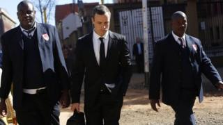 Oscar Pistoriu (C) leaves court escorted by two private security officers in Pretoria, Monday 7 July 2014